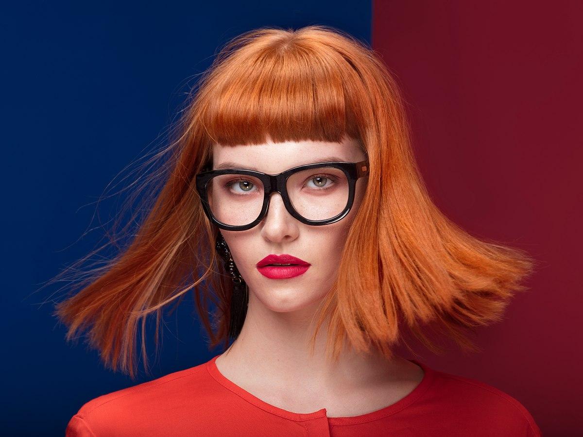 Femme rousse avec une frange courte et des lunettes