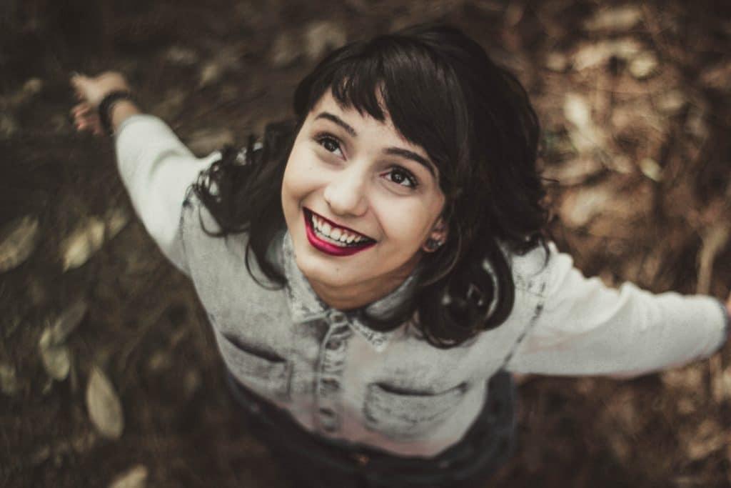 Femme au visage rond et une frange dégradée, heureuse qui sourit